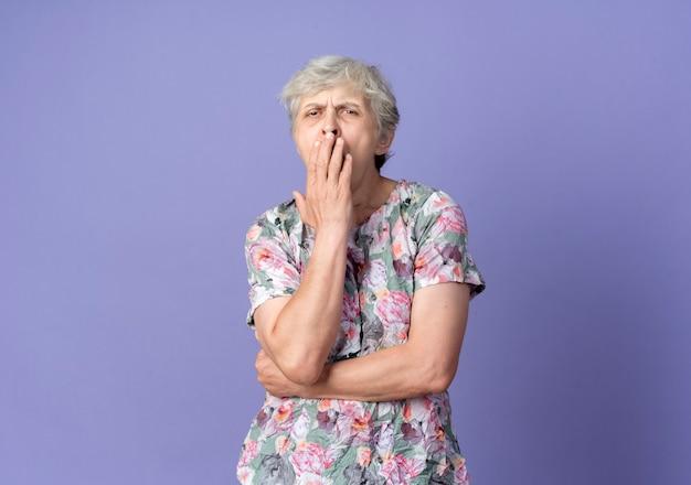 Senna starsza kobieta ziewa i trzyma usta na białym tle na fioletowej ścianie