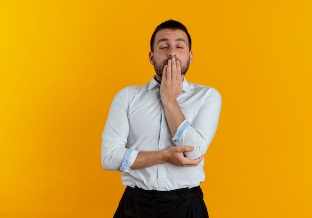 Senny przystojny mężczyzna kładzie dłoń na ustach z zamkniętymi oczami na białym tle na pomarańczowej ścianie