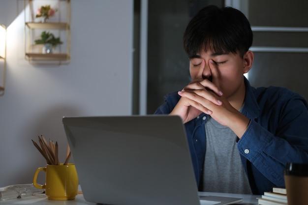 Senny, wyczerpany kolaż młody człowiek pracuje w godzinach nadliczbowych przy biurku z laptopem, ma zamiar zasnąć, brak snu i koncepcja pracy w nadgodzinach.
