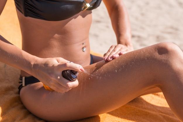 Sensous szczupła kobieta stosowania oleju opalania