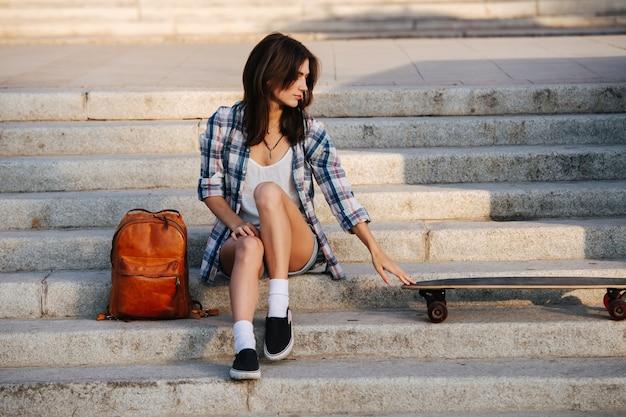 Sentymentalna kobieta siedzi na schodach i patrzy ostrożnie na swoją deskorolkę