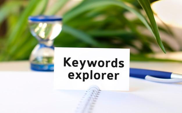 Seo biznes koncepcja tekst na biały notatnik i klepsydra, niebieski długopis, zielone kwiaty