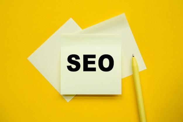Seo - na żółtych kostkach i kartce, żółty długopis na żółtej ścianie, jasne rozwiązanie dla koncepcji biznesowej, finansowej, marketingowej
