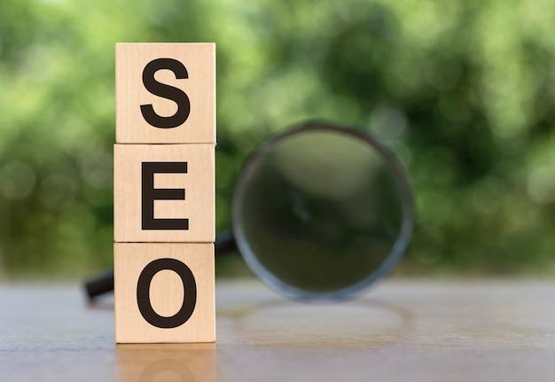 Seo search engine optimization tekst drewniane kostki i szkło powiększające na drewnianym stole