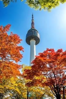 Seoul tower i czerwone jesienne liście klonu na górze namsan w korei południowej