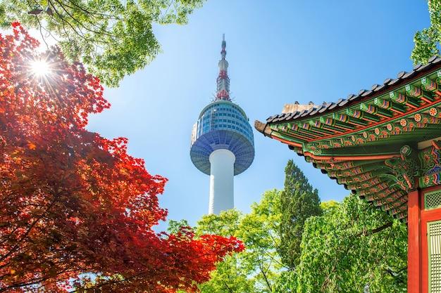 Seoul tower z dachem gyeongbokgung i czerwonymi jesiennymi liśćmi klonu na górze namsan w korei południowej