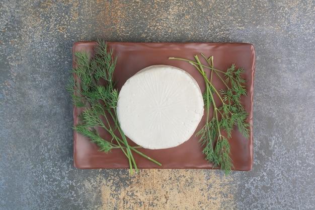 Ser biały na brązowym talerzu z koperkiem.