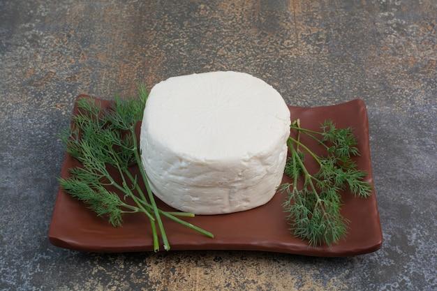 Ser biały na brązowym talerzu z koperkiem