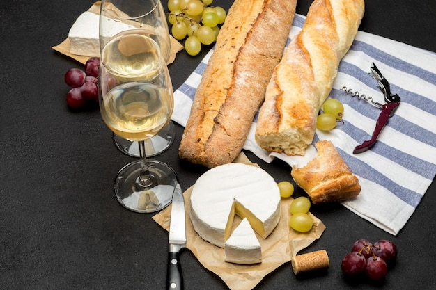 Ser brie, bagietka i dwie szklanki białego wina na ciemnym tle betonu