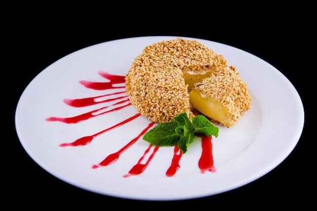 Ser brie smażony w głębokim tłuszczu z sezamem udekorowany listkiem świeżej mięty i sosem borówkowym.