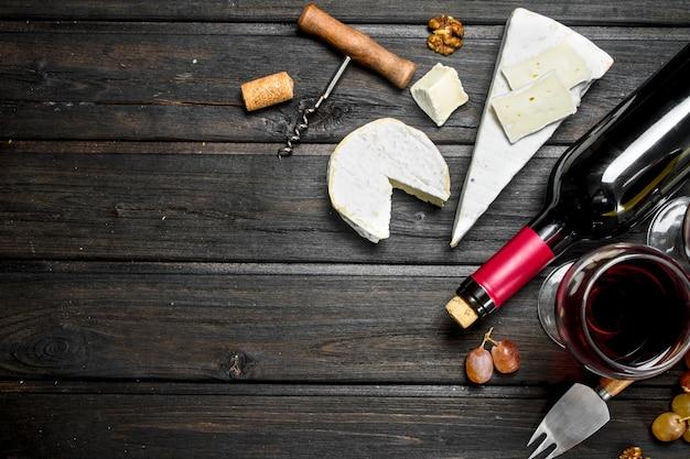 Ser brie z czerwonym winem, orzechami i winogronami na drewnianym stole.