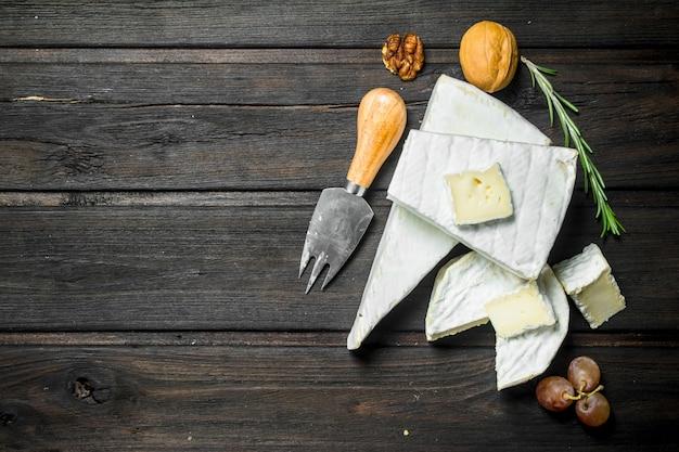Ser brie z nożem. na drewnianym.