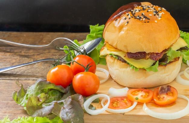 Ser burger domowej roboty z mięsem na drewnianym talerzu i warzywami, pomidor.