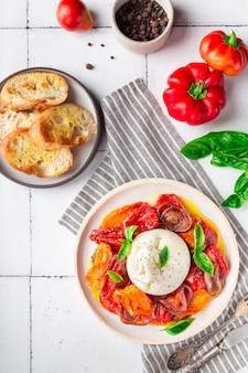 Ser burrata z pieczonymi pomidorami, papryką, czerwoną cebulą i świeżą bazylią na białym tle płytek