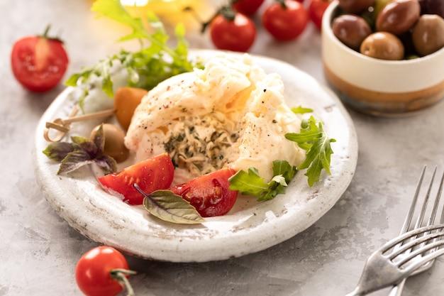 Ser burrata z rukolą, pomidorami koktajlowymi i oliwkami na okrągłym białym talerzu