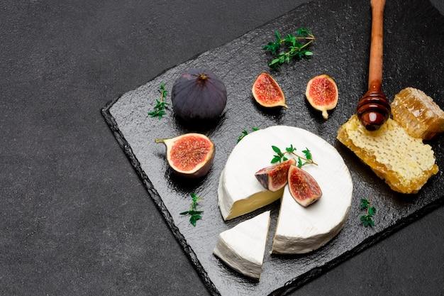 Ser camembert i plasterek wycięty na kamiennej desce