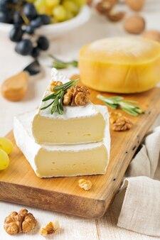 Ser camembert układać z winogronami, orzechami włoskimi i bazylią na szarym tle z jasnego betonu lub kamienia
