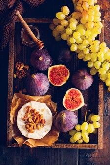 Ser camembert z figami, orzechami włoskimi, miodem i tymiankiem podawany na obiad w ciemnym tonie na drewnianej powierzchni w stylu retro