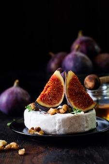 Ser camembert z figami, orzechami włoskimi, miodem i tymiankiem podawany na obiad w ciemnym tonie