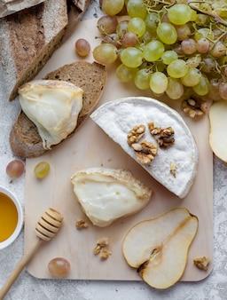 Ser camembert z zielonymi winogronami, miodem, gruszką i orzechami. widok z góry