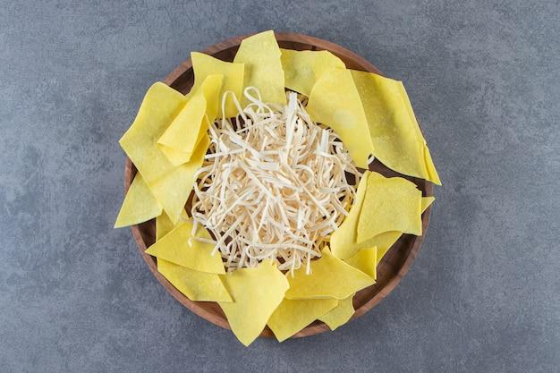 Ser cecil i arkusze lasagne na drewnianym talerzu, na marmurowej powierzchni.