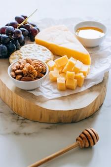 Ser cheddar, winogrona, orzechy, miód i krakingu w desce na marmur