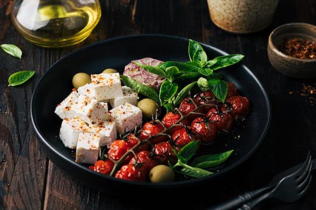 Ser feta i pieczone pomidorki koktajlowe sałatka z bazylią i oliwkami selektywne focus