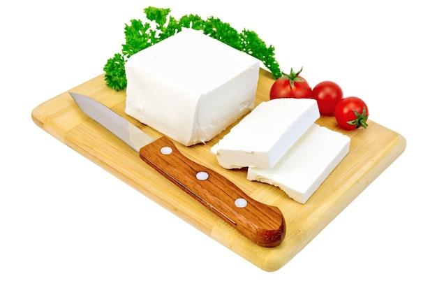 Ser feta, nóż, pietruszka i pomidory na drewnianej desce na białym tle