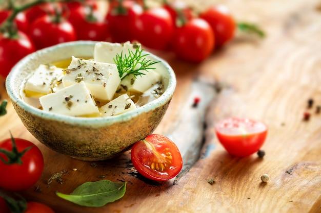 Ser feta w misce z oliwą na desce do krojenia z oliwkami, koperkiem i pomidorkami koktajlowymi, miejsce na kopię