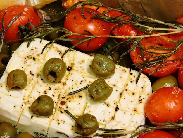 Ser feta z oliwkami, rozmarynem i pomidorami cherry na papierze do pieczenia.