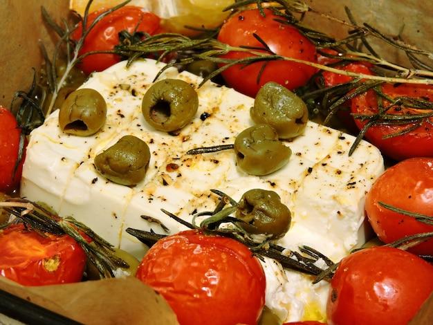 Ser feta z oliwkami, rozmarynem i pomidorami cherry.