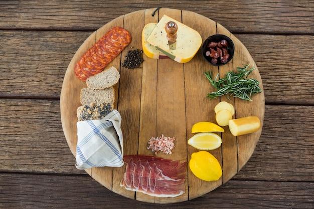 Ser gouda, słodka limonka, mięso, kromki chleba, czarny pieprz i rozmaryn na desce