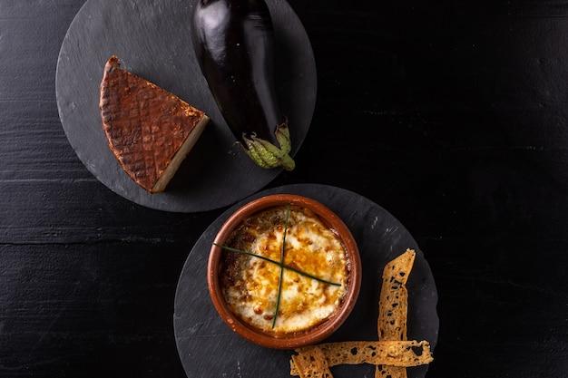 Ser i bakłażan w piekarniku z czarnym tłem - gastronomia - czarne tło.
