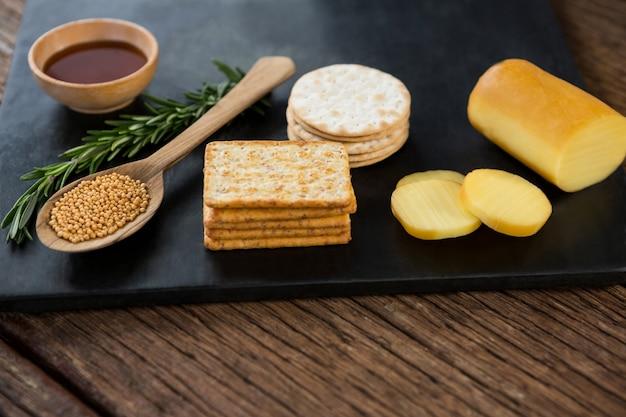 Ser, krakersy, chipsy nacho i zioła rozmarynu na talerzu łupkowym