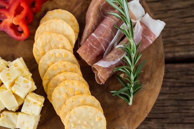 Ser, plastry czerwonej papryki, mięso i chipsy nacho na drewnianym stole