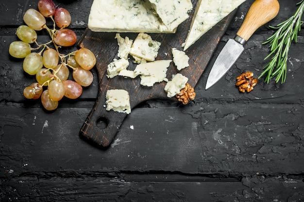 Ser pleśniowy z winogronami i rozmarynem na czarnym drewnianym stole.