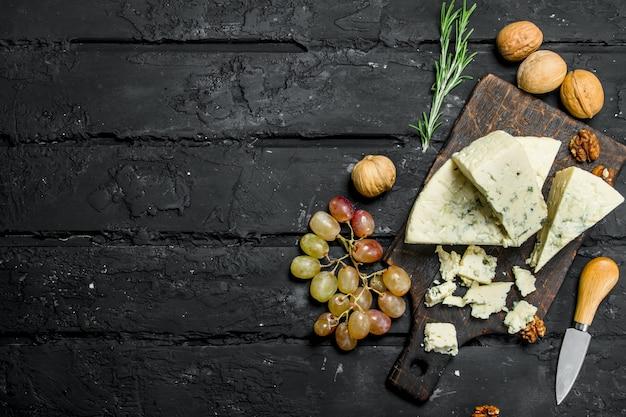 Ser pleśniowy z winogronami i rozmarynem. na czarnym tle rustykalnym.