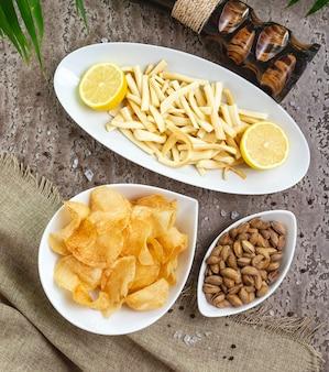 Ser sznurkowy z cytryną w misce podany z frytkami i pistacjami