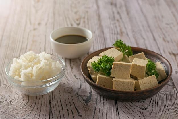 Ser tofu z sosem sojowym i ryżem na drewnianym stole w słońcu
