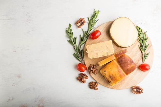 Ser wędzony i różne rodzaje serów z rozmarynem i pomidorami na desce na białej powierzchni drewnianej