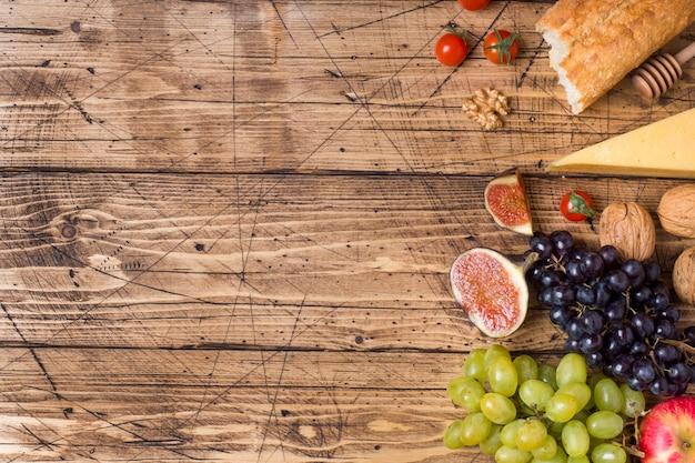 Ser, wino, bagietki winogrona figi miód i przekąski na rustykalnym drewnianym blacie z miejsca na kopię.