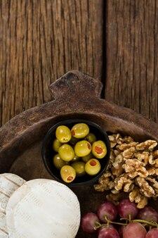 Ser, winogrona, oliwki i orzech na drewnianym talerzu