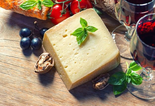 Ser z czerwonym winem, orzechami włoskimi i winogronami. tło żywności. obraz w stylu niskiego klucza