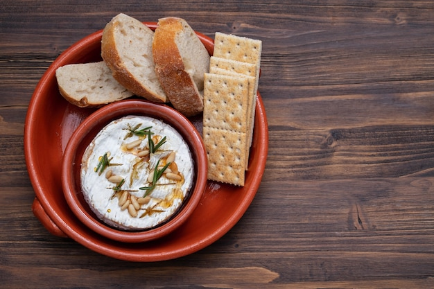 Ser z ziołami, orzechami i miodem w naczyniu ceramicznym