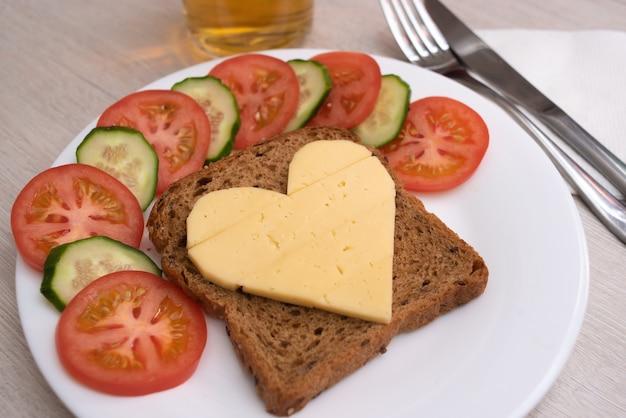 Serca kanapka z serem z warzywami na białym talerzu