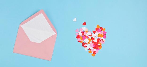 Serca konfetti i różowa koperta.