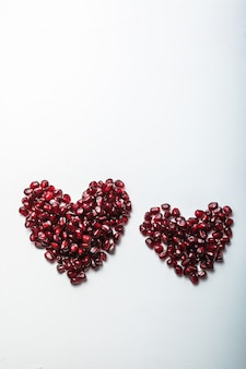 Serca kształt nasion granatu na białym tle.