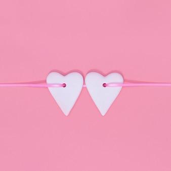 Serca obok siebie na różowej wstążce w pastelowym różu