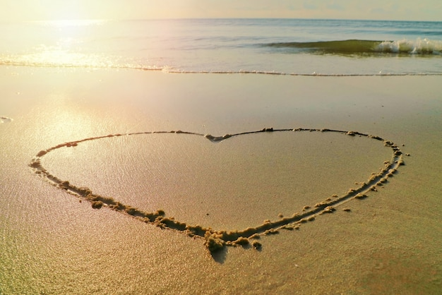 Serca z falami uderzają o plażę i słońce w letni poranek