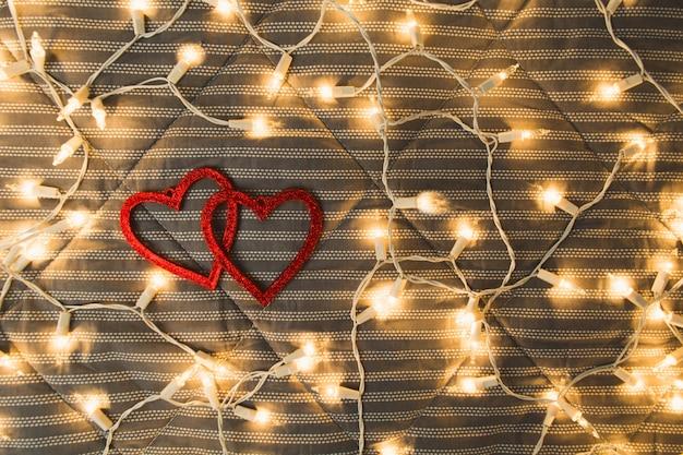 Serca z girlandami świecącymi nad przytulną kratą